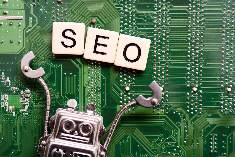 Ein Roboter hält die Buchstaben SEO hoch, im Hintergrund ist eine Platine