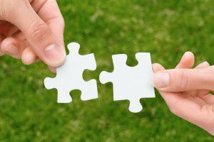 Zwei Hände halten zwei Puzzlestücke aneinander