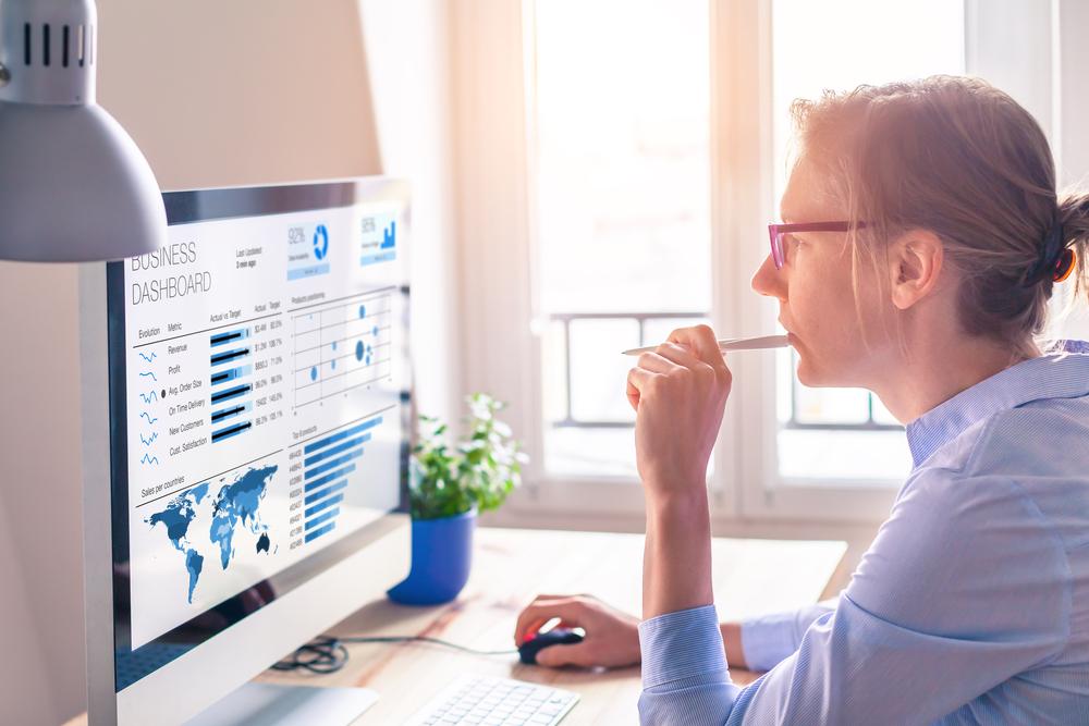 Frau vor einem Bildschirm mit Statistiken