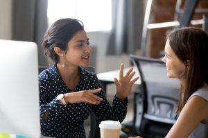 Zwei junge Frauen unterhalten sich im Büro über eine Idee