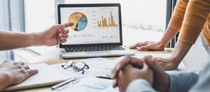 Drei Menschen sehen sich Statistiken und Grafiken auf einem Bildschirm an
