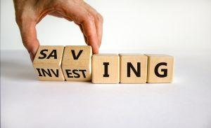 Würfel mit Buchstaben, die die Worte Saving und Investing zeigen