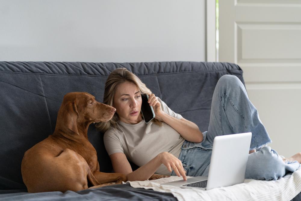 Telefonierende Frau mit Hund und LapTop am Sofa