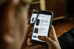 Mann, der sich am Handy auf Amazon Jacken ansieht